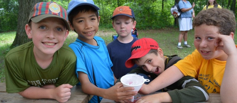 Day Camp scouts take a short snack break during an afternoon of fun at Camp Oakarro.